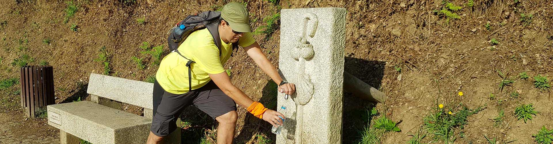 pilgrim refilling water on the way from Tui on the portuguese camino