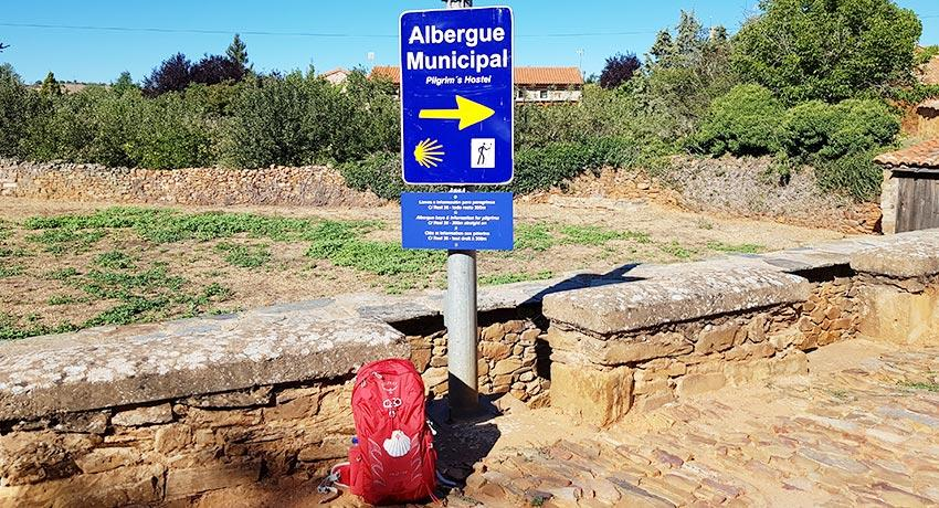 backpack by albergue sign on the camino from leon
