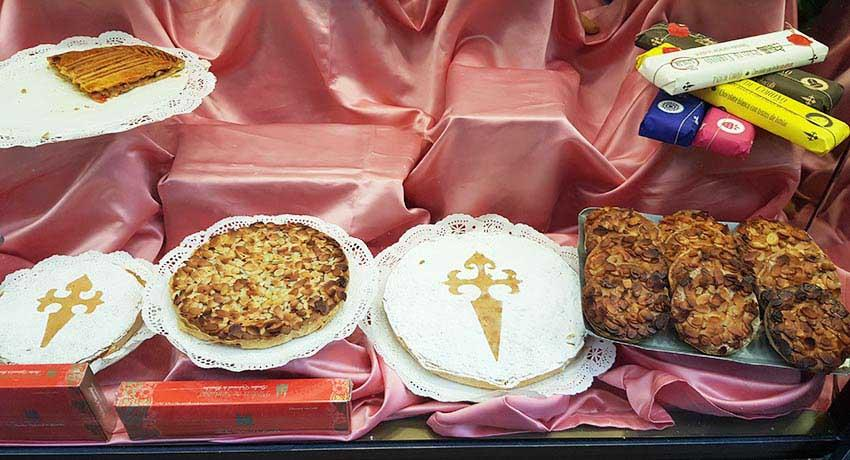 santiago almond cake on a display with typical desserts