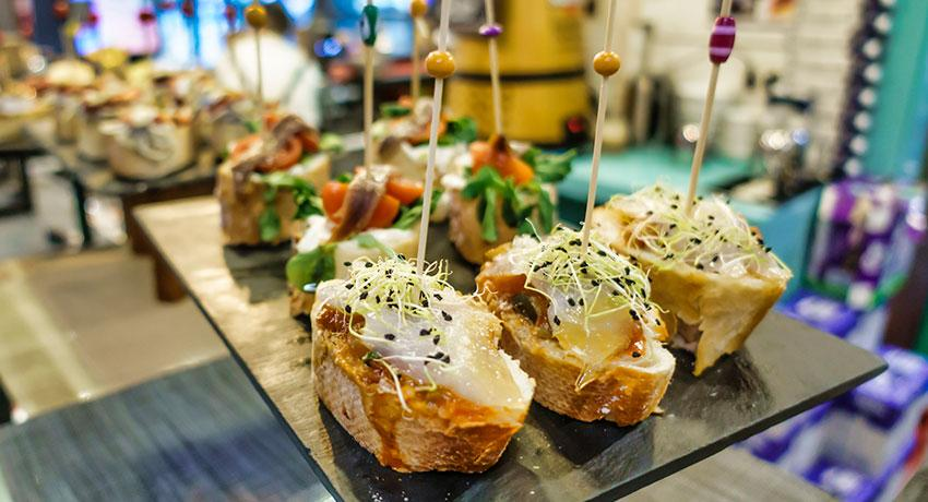 assorted pintxos displayed on a bar